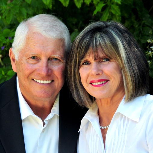 Older couple stand near each other while smiling.