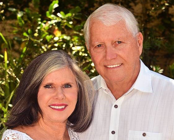 Jim and Debbie Hogan of Standing Stone Ministry stand together outside dressed in white and smiling.