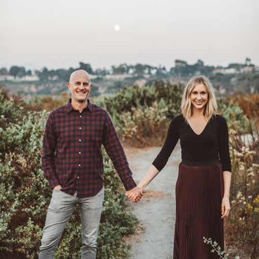 Sharp looking couple hold hands while standing outside in a rural setting.