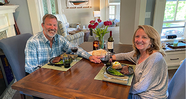 Middle aged couple hold hands across a dining table while smiling .