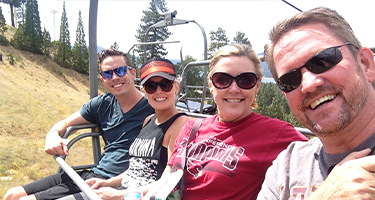 Two couples smile while sitting in a gondola carriage.