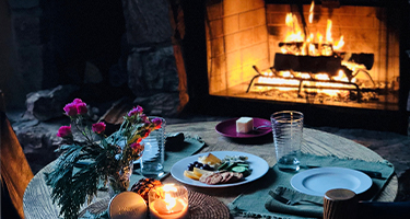 A dining table is romantically set in front of a fireplace.