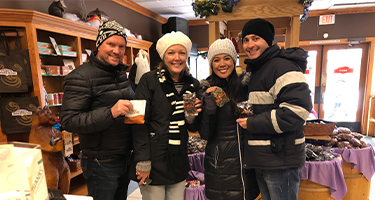 Two couples stand smiling while dressed in winter garb inside.